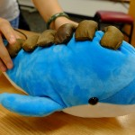 The Musical Dolphin is a plush animal that changes pitch response as the backbone is stroked and sound style changes when the fins are squeezed. It produces soothing environmentally-inspired sounds. Students looked at the pros and cons of doll therapy and robot therapy as part of their design process
